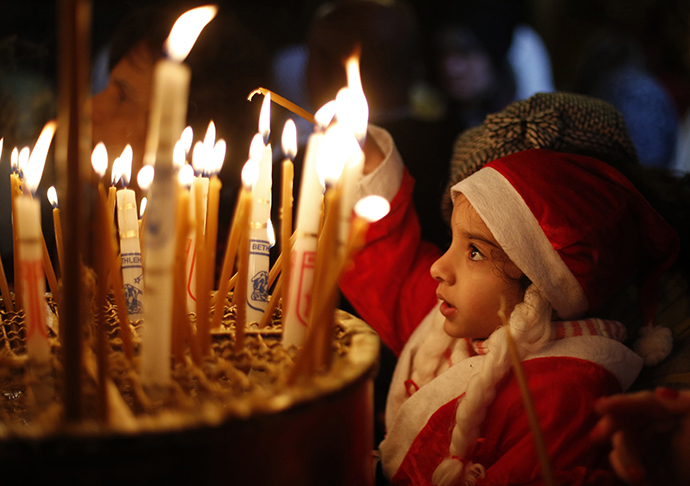 A child wearing a Santa Claus costume lights a candle inside the Church of the Nativity in Bethlehem during the Eastern Orthodox Christmas