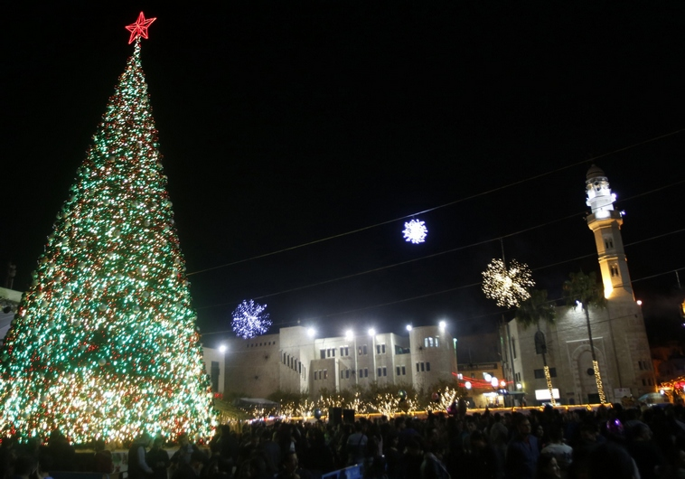 a christmas tree stands in the courtyard of the nativity church in the west bank town